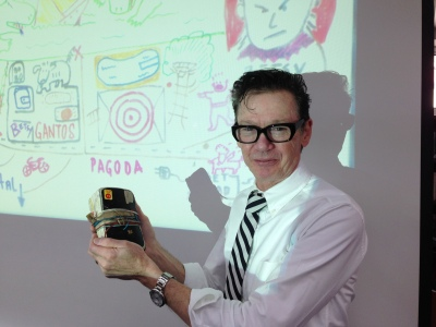 Jack Gantos with his journal in front of map marked with significant incidents of his childhood.